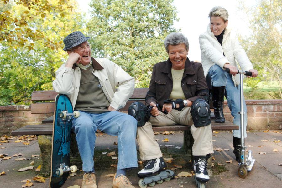 Ein Mann mit Hut und Skateboard, eine Frau mit Inline-Skatern und eine Frau mit einem Roller.