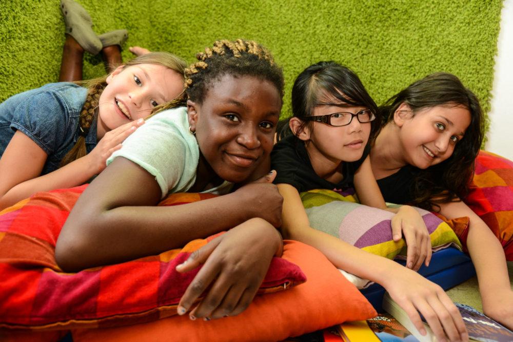 4 Mädchen unterschiedlicher Herkunft liegen auf einer Kissenlandschaft