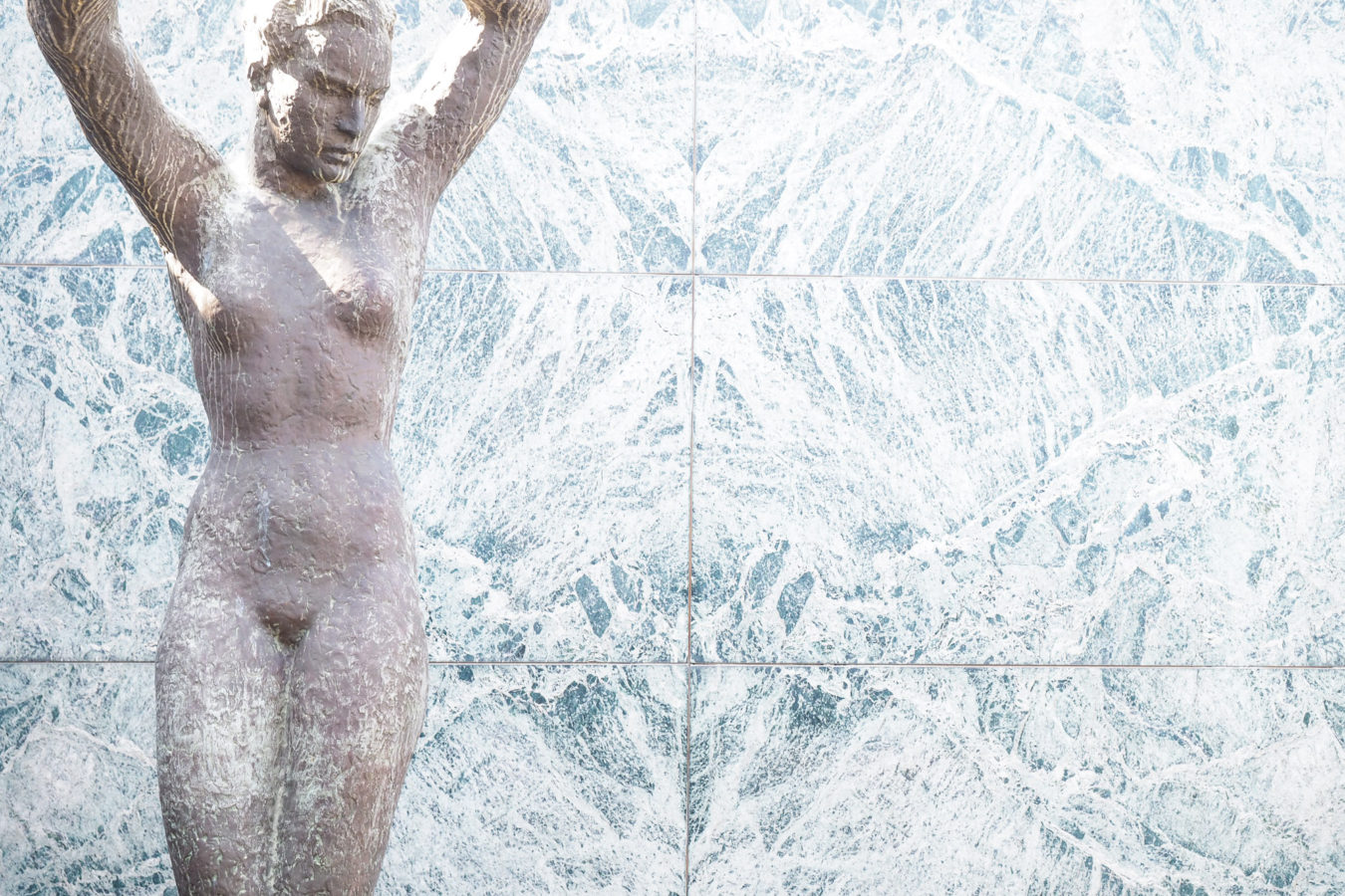 Eine weibliche Skulptur steht vor einer Marmorwand.