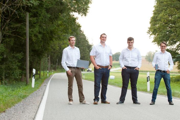 Vier Männer mit weißen Hemden stehen mit einem tablet-PC auf einer Landstraße. Ein Auto fährt von hinten heran
