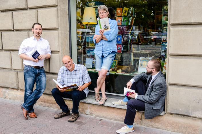 Drei Männer und eine Frau sitzen und stehen mit Büchern in den Händen vor dem Schaufenster eines Buchladen.