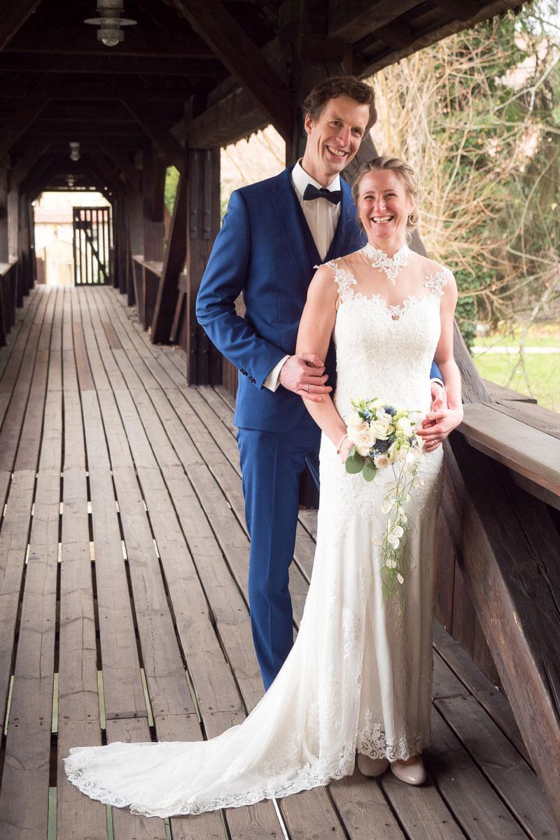 stehendes Hochzeitspaar auf Brücke