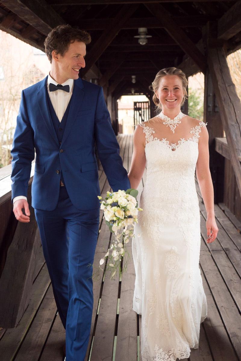 Hochzeitspaar läuft nebeneinader eine Brücke entlang
