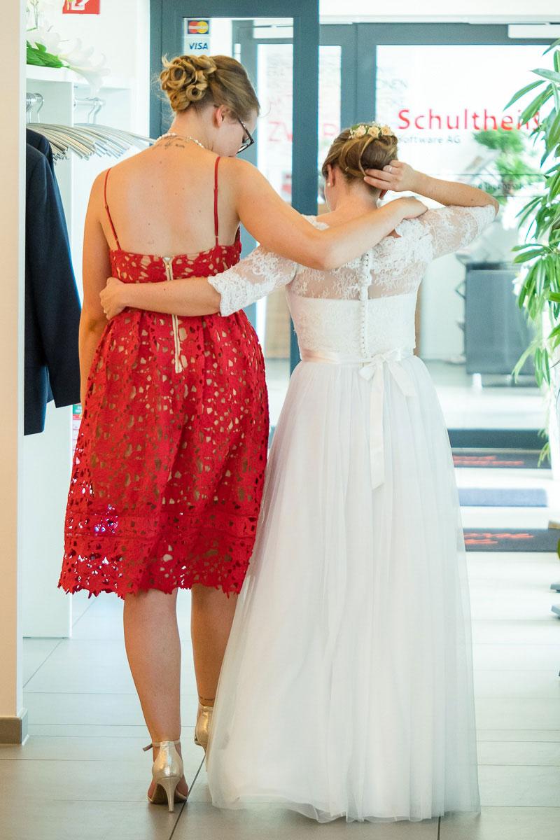 Braut in weiß hält ihre Freundin in rot im Arm