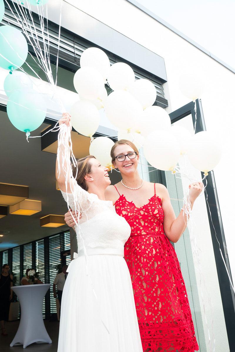 Braut und ihre Freundin halten Luftballons hoch