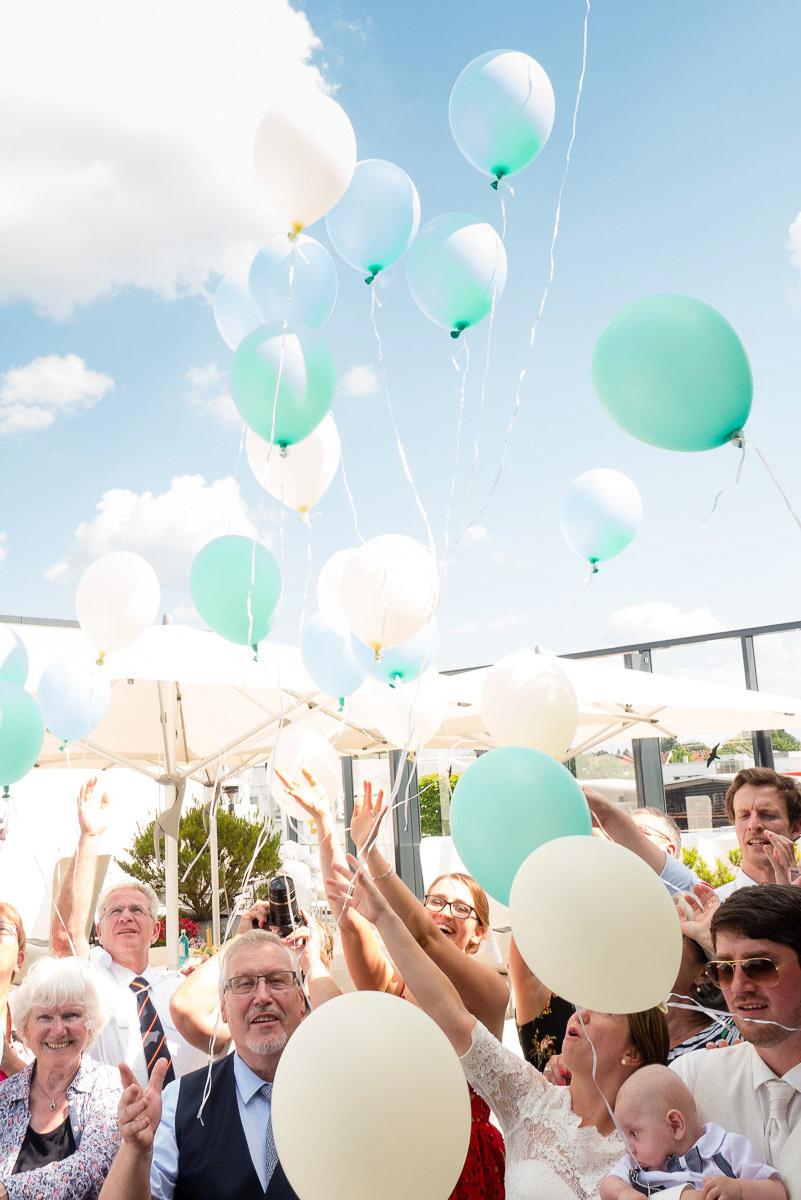 Mintfarbende und weiße Luftballons steigen in den Himmel