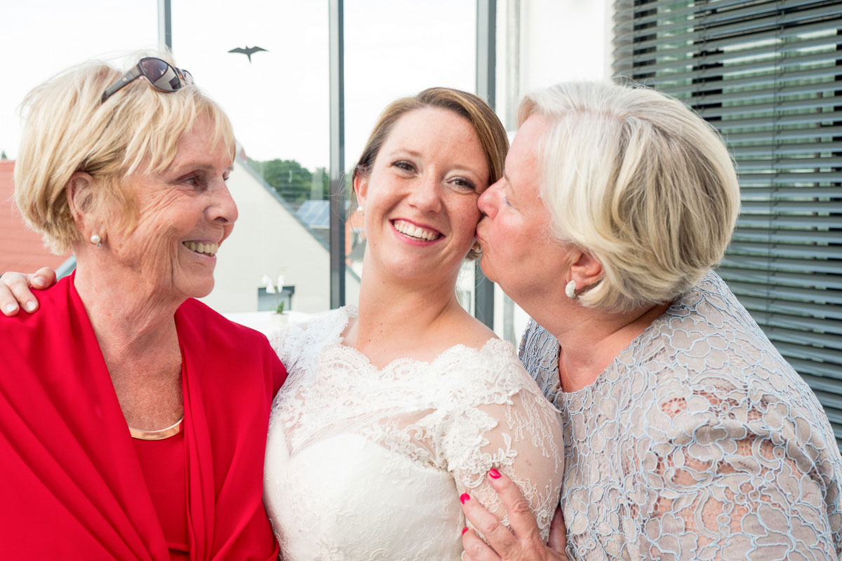 Braut wird von der Mutter auf die Wange geküsst