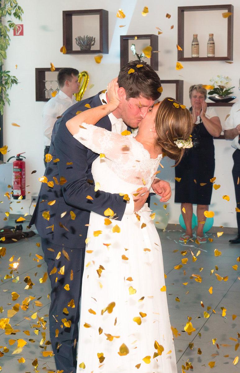 küssendes Hochzeitspaar im Blumenregen