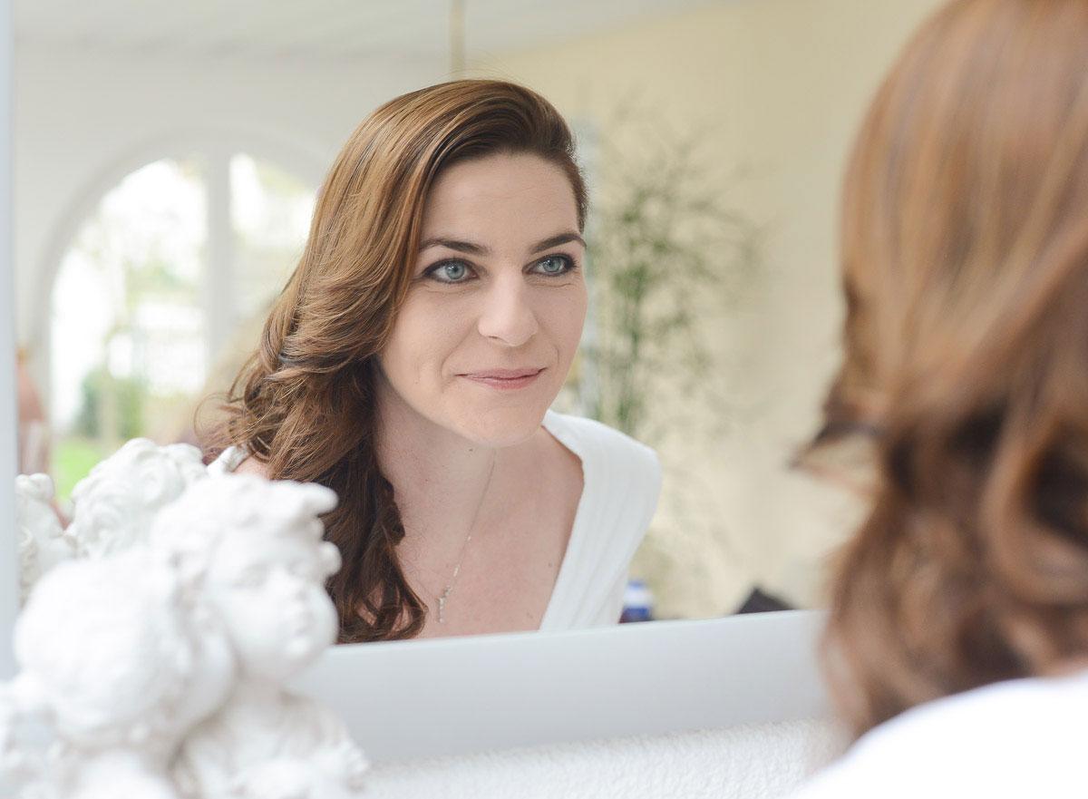 Braut sieht sich im Spiegel an