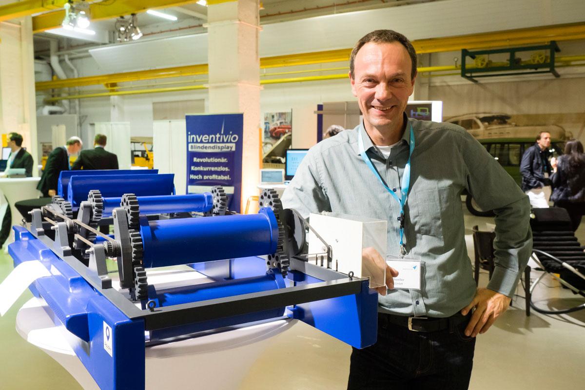 Mann neben einer Maschine auf der Demonight der BayStartup GmbH