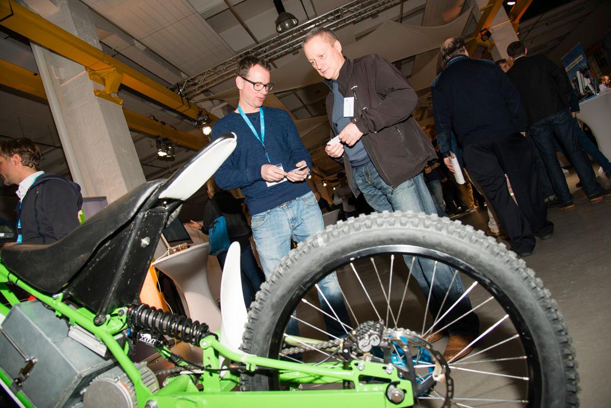 zwei Messebesucher mit einem Fahrrad im Vordergrund