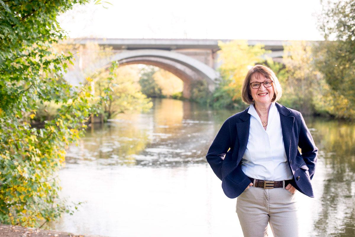 Portrait einer Frau vor einer Brücke