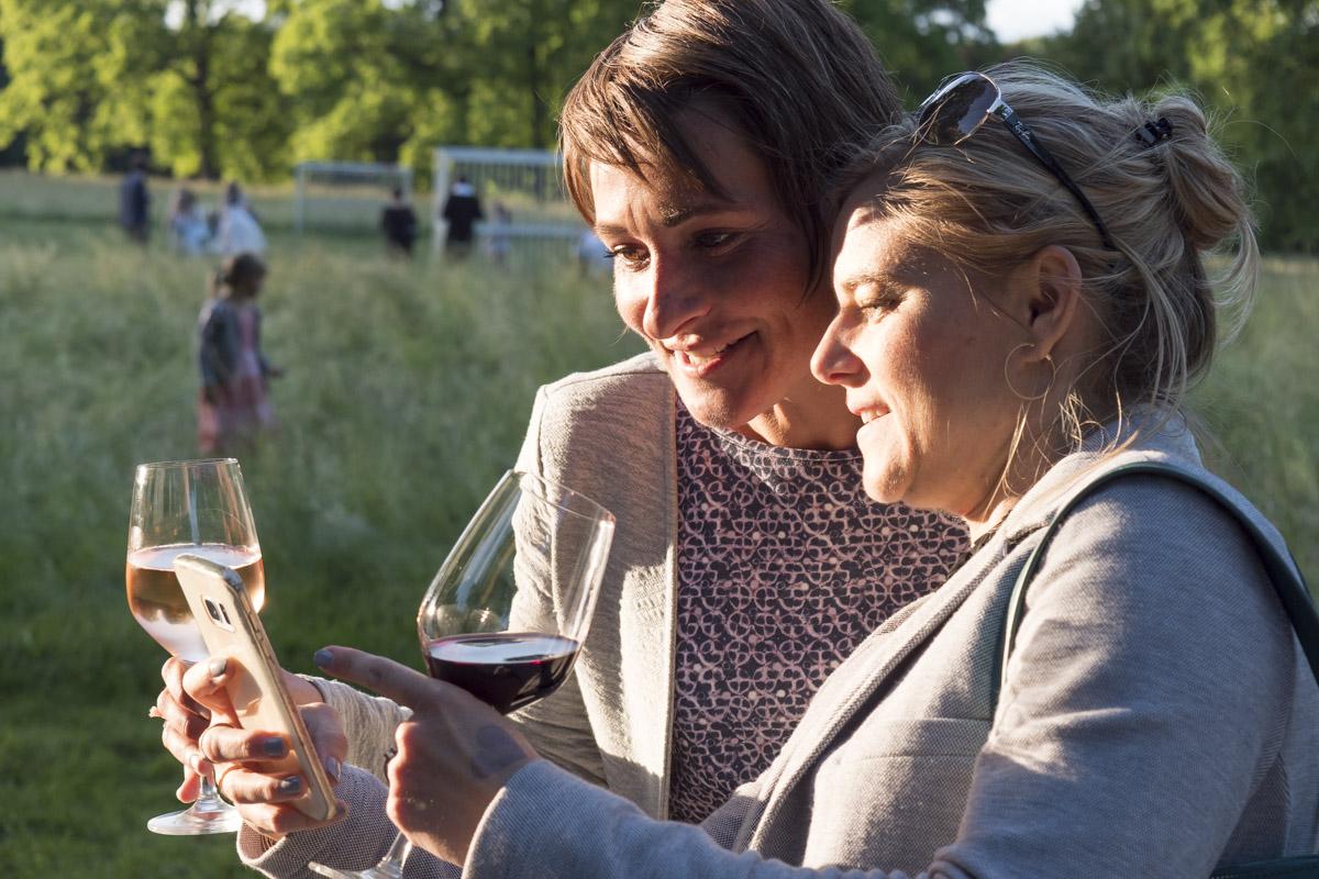 zwei Frauen mit Weingläsern schauen auf ein Smartphone